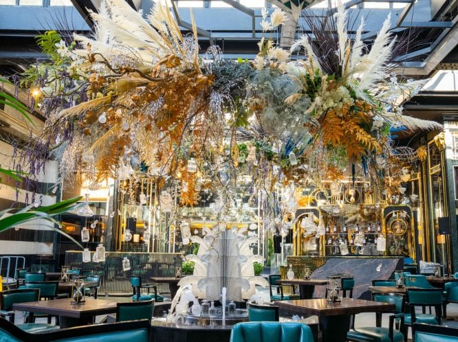 A wide view of Solas, the opulent, floral-inspired dining terrace at The Savoy Hotel.