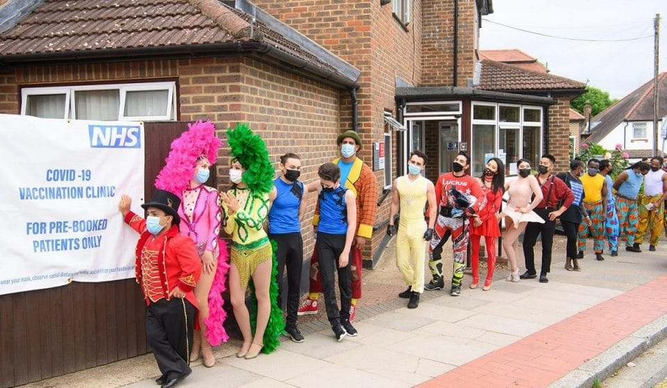 A Group Of Circus Performers Lined Up To Get Vaccinated In Full Costume