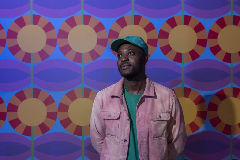 Yinka Ilori poses in front of a colourful wall at Dodge, the new installation at Somerset House.