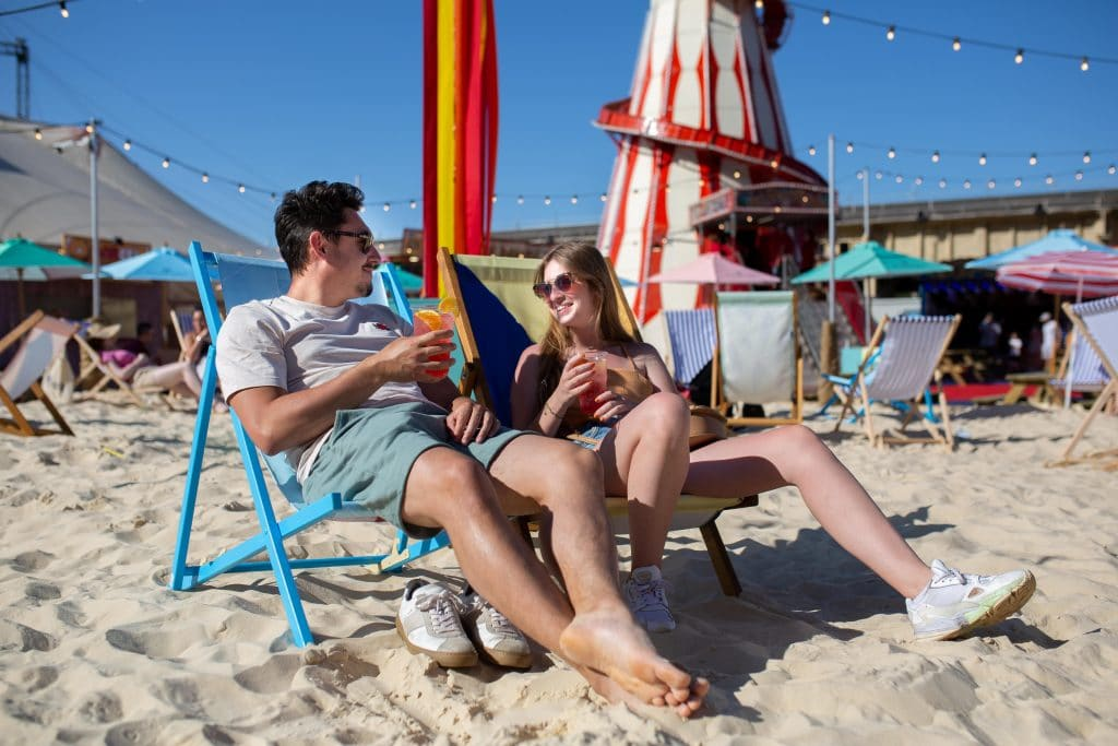 A couple relaxes on the sand at London Wonderground