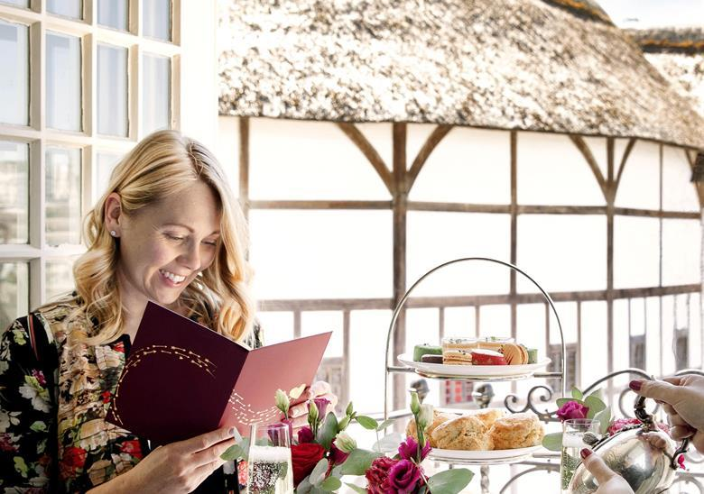 A woman reads a menu at The Globe afternoon tea experience.