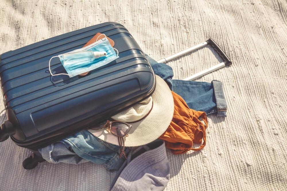travel-ban-suitcase-sand