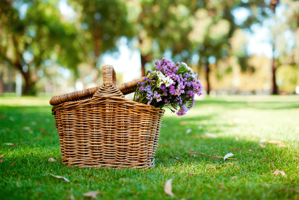 picnic basket with flowers on grass