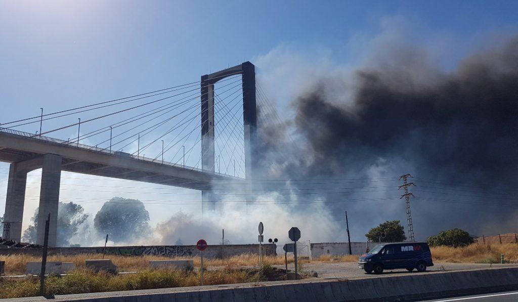 Una enorme columna de humo cubre el puente del Centenario en Sevilla