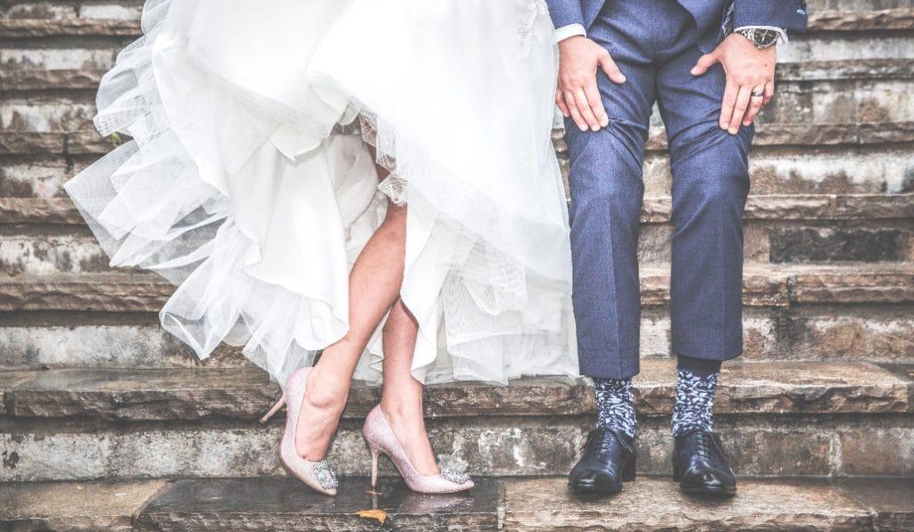 Dos camareros escoltan a una novia con una sombrilla en la plaza del Salvador