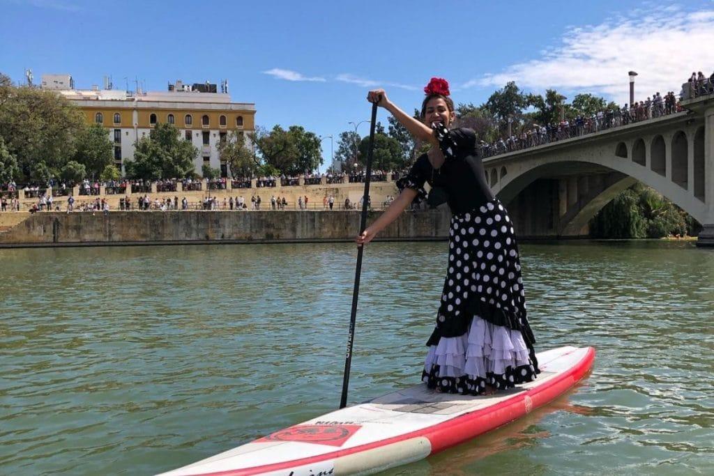 Una mujer vestida de flamenca recorre el Guadalquivir haciendo paddle surf